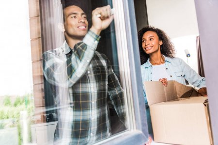 Photo for African american husband opening window while wife opening box and looking at husband - Royalty Free Image