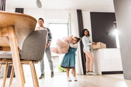 Photo pour Vue à faible angle de la famille afro-américaine marchant dans la maison tout en tenant des choses différentes - image libre de droit