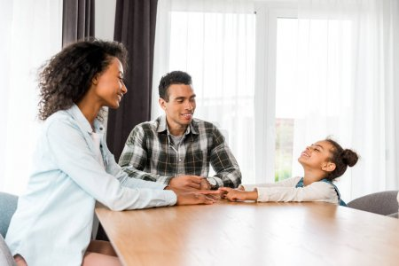 Photo for African american family sitting before table, smiling and looking at each other - Royalty Free Image