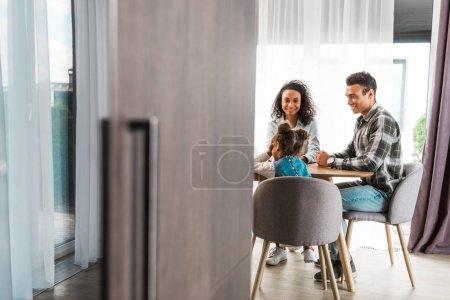 Photo pour Foyer sélectif de la famille afro-américaine assis devant la table tandis que la femme regardant la caméra - image libre de droit