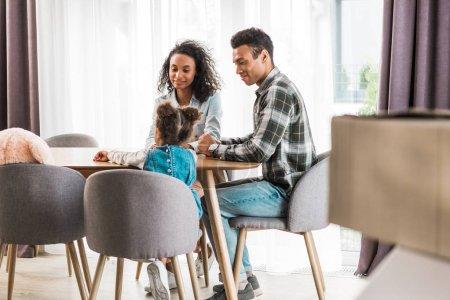Photo pour Foyer sélectif de la famille afro-américaine assis devant la table, souriant et se regardant - image libre de droit