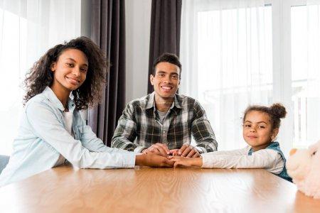 Photo pour Afro-américaine famille assis devant la table, souriant et regardant la caméra - image libre de droit