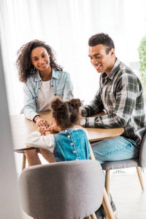 Photo pour Afro-américaine famille assis devant la table tandis que la mère regardant caméra et père regardant enfant - image libre de droit