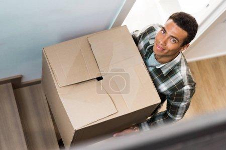 Foto de Vista de ángulo alto de guapo hombre afroamericano sosteniendo la caja mientras que va arriba y mirando a la cámara - Imagen libre de derechos
