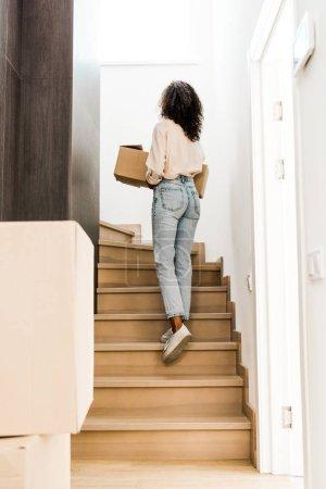 Photo pour Vue arrière de la femme marchant à l'étage tout en retenant la boîte - image libre de droit