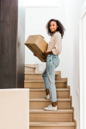 Photo for Full length view of african american woman walking upstairs while holding box and looking at camera - Royalty Free Image