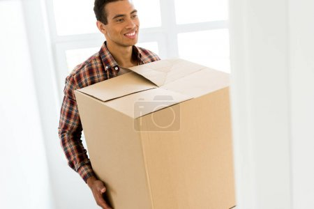 Photo for Selective focus of african american man holding box while walking into room - Royalty Free Image