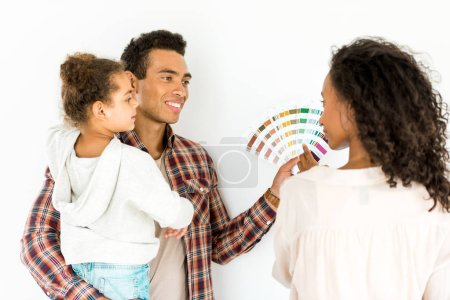 Afrikanisch-amerikanischer Mann hält Kind und bunte Palette, während Frau Mann ansieht