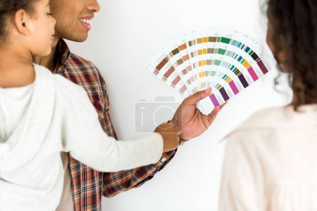 Photo for Cropped view of african american wife and husband trying to choose color for wall while man holding kid - Royalty Free Image