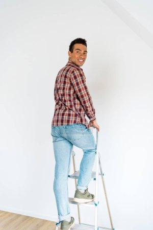 Foto de Vista de longitud completa de hombre afroamericano guapo de pie en la escalera y mirando a la cámara - Imagen libre de derechos