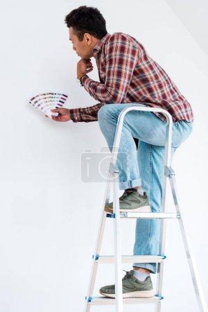 Afrikanisch-amerikanischer Mann steht an der Leiter und schaut auf bunte Palette isoliert auf weiß