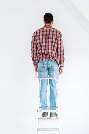 Photo pour Vue arrière de l'homme restant à l'échelle et regardant le mur isolé sur le blanc - image libre de droit