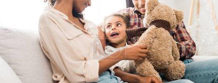 Photo pour Tir panoramique de la famille américaine africaine s'asseyant sur le sofa tandis que l'enfant retenant l'ours de nounours et regardant la mère - image libre de droit