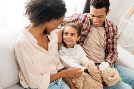 Photo for African american parents looking at kid holding teddy bear while sitting on sofa - Royalty Free Image