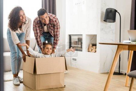 Photo pour Vue pleine longueur des parents américains africains jouant avec l'enfant tandis que l'enfant s'asseyant dans la boîte - image libre de droit