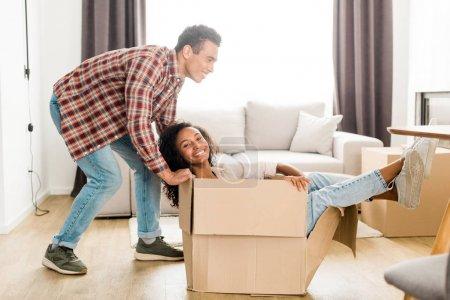 Photo pour Vue pleine longueur du mari afro-américain essayant de déplacer la boîte avec sa femme - image libre de droit
