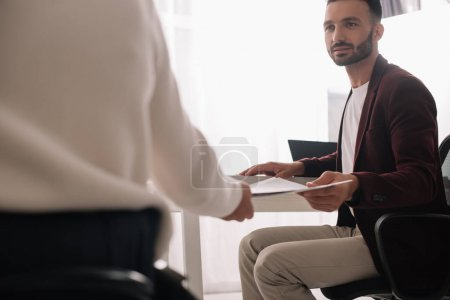Photo for Handsome businessman giving documents to disabled businesswoman in office - Royalty Free Image