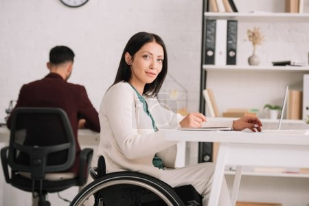 Photo for Smiling disabled businesswoman looking at camera while sitting in wheelchair at workplace - Royalty Free Image