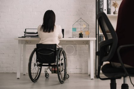 Photo for Back view of disabled businesswoman sitting at workplace in wheelchair - Royalty Free Image
