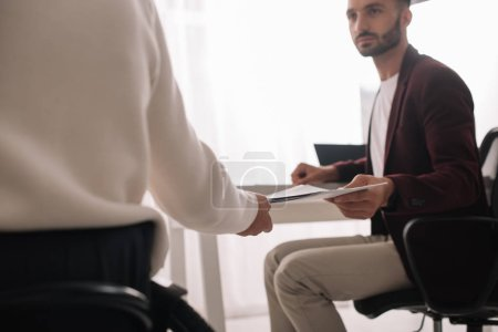 Photo for Partial view of disabled businesswoman giving documents to handsome colleague - Royalty Free Image