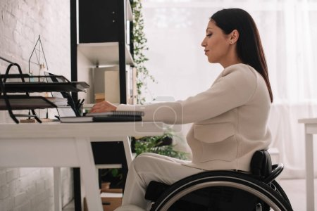 Photo for Attractive disabled businesswoman using laptop while sitting in wheelchair at workplace - Royalty Free Image
