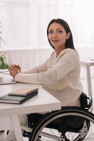 Photo for Cheerful disabled businesswoman looking at camera while sitting at workplace - Royalty Free Image