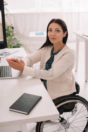 Photo for Beautiful disabled businesswoman smiling at camera while sitting at workplace in wheelchair - Royalty Free Image