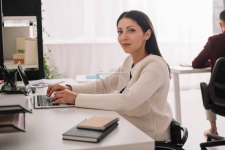 Photo for Attractive disabled businesswoman looking at camera while sitting at workplace in office - Royalty Free Image