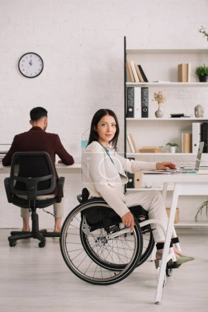 Photo for Beautiful disabled businesswoman looking at camera while sitting in wheelchair near colleague - Royalty Free Image