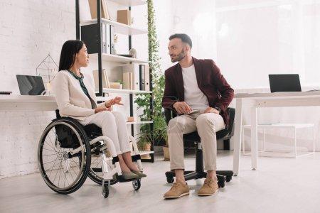 Photo pour Femme d'affaires handicapée en fauteuil roulant gestuelle tout en parlant à un partenaire d'affaires au bureau - image libre de droit