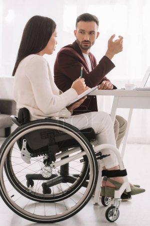 Photo pour Femme d'affaires handicapée tenant un crayon et un cahier tout en parlant avec un partenaire d'affaires au bureau - image libre de droit