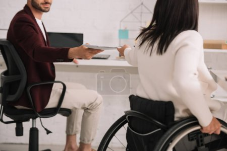 cropped view of disabled businesswoman giving documents to colleague in office