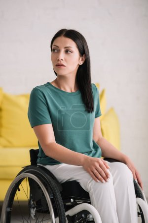 Photo for Serious disabled woman looking away while sitting in wheelchair at home - Royalty Free Image
