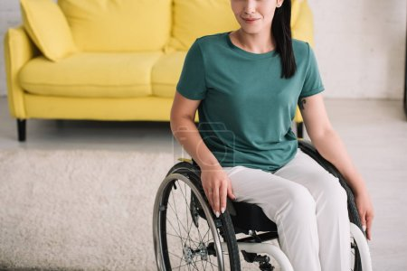 Photo pour Vue recadrée de femme handicapée de sourire s'asseyant dans le fauteuil roulant à la maison - image libre de droit