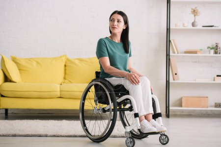 Photo for Positive, smiling disabled woman looking away while sitting in wheelchair at home - Royalty Free Image