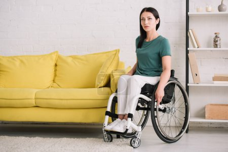 Photo pour Grave, jeune femme handicapée regardant loin alors qu'elle était assise en fauteuil roulant à la maison - image libre de droit