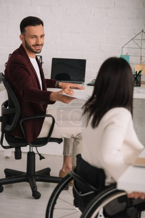 handsome businessman giving documents to disabled businesswoman in office
