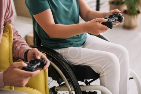 Photo for KYIV, UKRAINE - JULY 10, 2019:  Cropped view of young disabled woman playing video game with boyfriend at home. - Royalty Free Image