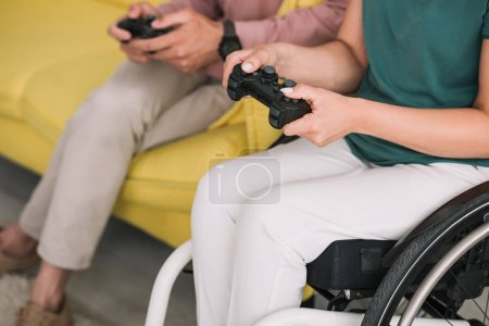 Photo for KYIV, UKRAINE - JULY 10, 2019: Partial view of disabled woman playing video game with boyfriend at home. - Royalty Free Image