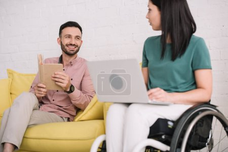 Photo for Pretty, disabled woman using laptop near cheerful boyfriend sitting on sofa with book - Royalty Free Image