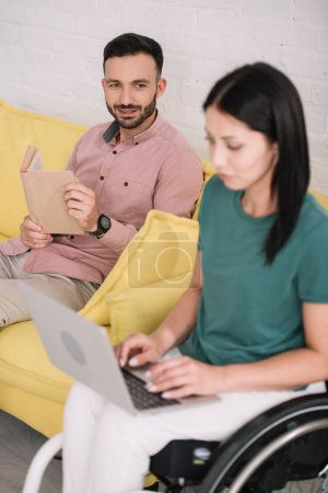 Photo for Attentive disabled woman using laptop near smiling boyfriend sitting on sofa with book - Royalty Free Image