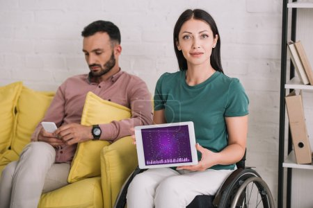 Photo for Smiling disabled woman showing digital tablet with infographics on screen while sitting near boyfriend using smartphone - Royalty Free Image