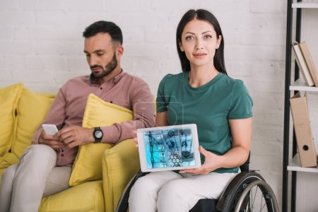 Photo for Young disabled woman showing digital tablet with dna information app while sitting near boyfriend using smartphone - Royalty Free Image