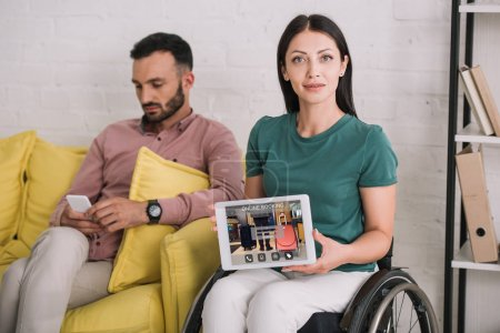 Photo for Smiling disabled woman showing digital tablet with booking online app while sitting near boyfriend using smartphone - Royalty Free Image