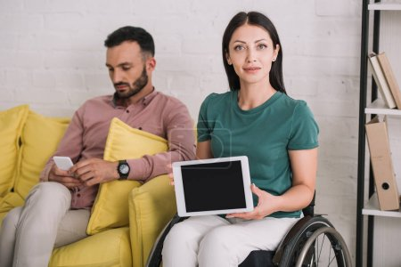 Photo for Attractive disabled woman showing digital tablet with blank screen while sitting near boyfriend using smartphone - Royalty Free Image