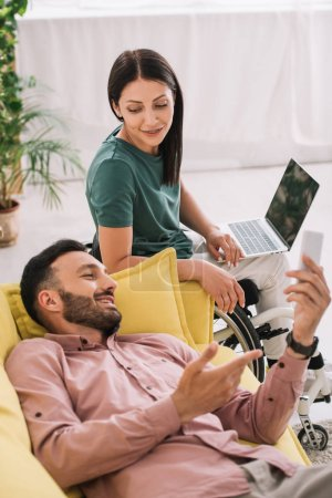 Photo for Smiling disabled woman using laptop while sitting near boyfriend lying on sofa with smartphone - Royalty Free Image