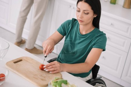 Photo for Young disabled woman cutting tomato on chopping board while preparing salad in kitchen - Royalty Free Image
