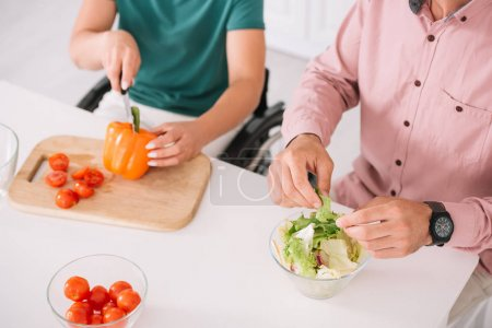Photo for Cropped view of disabled woman with boyfriend preaparing salad together - Royalty Free Image