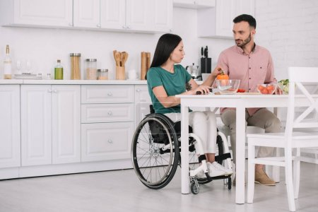 Photo for Young disabled woman with handsome boyfriend sitting at kitchen table and preparing salad together - Royalty Free Image