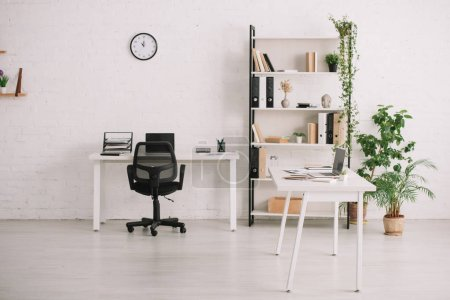 spacious office with desks, rack with books, plants in flowerpots and clock on white wall